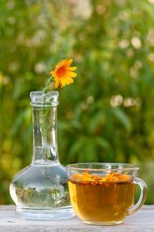 유리 플라스크에 줄기가 있는 금송화 꽃과 옆에 같은 꽃, 나무 판자에 있는 차 한 잔.