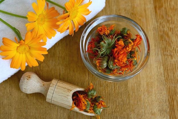 Цветки календулы лекарственной в деревянной миске. косметические продукты и цветы календулы на деревянном столе. спа-набор.