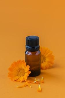 カレンデュラ製品。オレンジ色のエッセンシャルオイルと新鮮なキンセンカの花のボトル