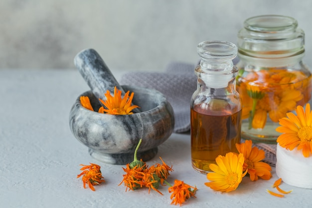 Calendula products. bottle of cosmetic, aromatic or essential oil and fresh and dry calendula flowers on light. aromatherapy, spa and wellness concept