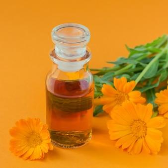 Продукты из календулы. бутылка косметического или эфирного масла и свежие цветы календулы на апельсине