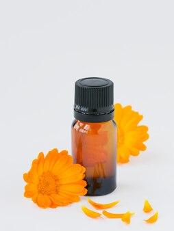 Продукты из календулы. бутылка эфирного масла и свежих цветов календулы на белом