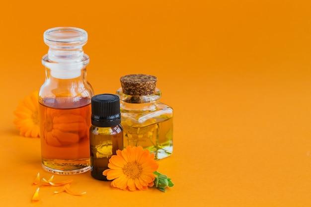 カレンデュラ製品。オレンジ色の化粧品、アロマオイルまたはエッセンシャルオイルと新鮮なキンセンカの花のボトル。アロマテラピー、スパ、ウェルネスのコンセプト