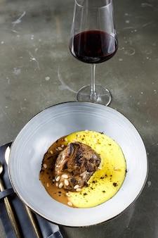Телячья щека в красном вине со сливочным баношем и запеченными вешенками