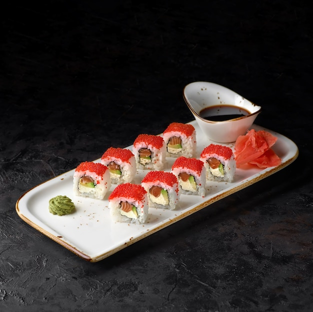 California maki sushi - ролл с сыром, авокадо, свежим лососем и икрой тобико на черном фоне.