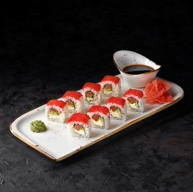 California maki sushi - roll with cheese, avocado, fresh salmon and tobiko caviar on black background.