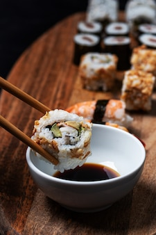 California roll sushi caught by chopsticks and being introduced into bowl of willow soybeans with more pieces of sushi around.