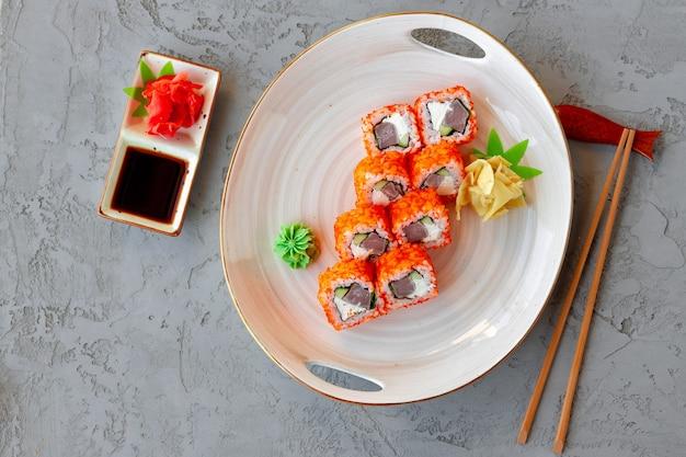 회색 테이블에 접시에 참치 일본 요리와 캘리포니아 롤