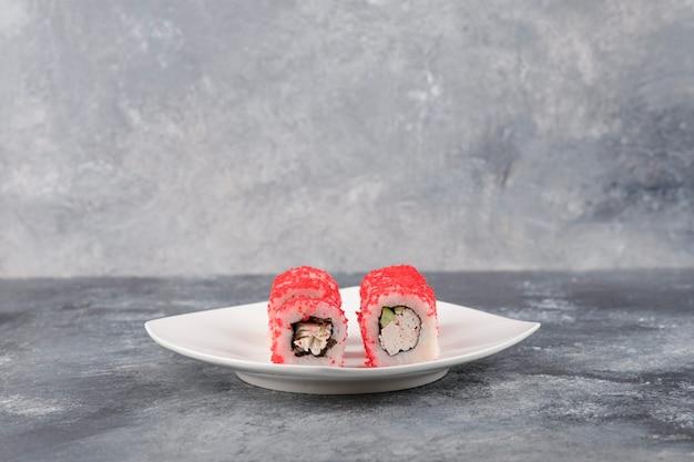 흰색 접시에 날치 캐 비어와 캘리포니아 롤