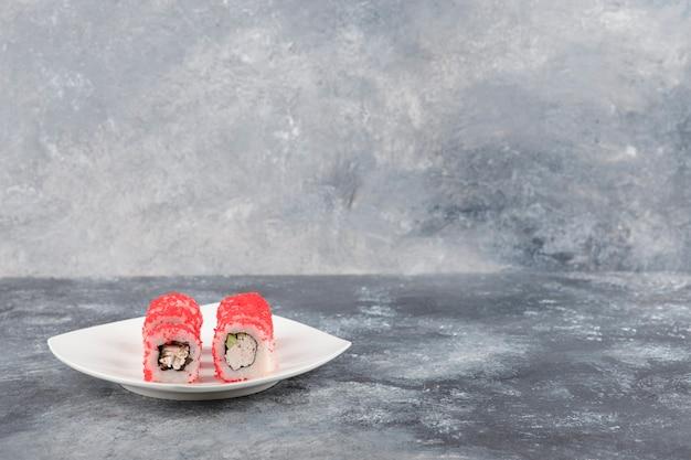 Involtini californiani con caviale di pesce volante su piatto bianco
