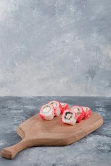California rolls con caviale di pesce volante su tavola di legno