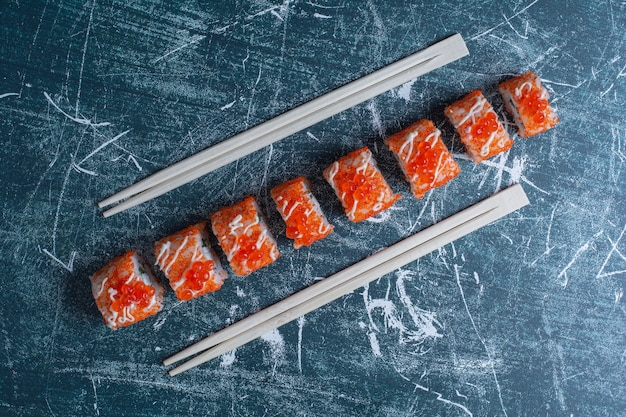 California sushi roll decorated with red caviar on blue with chopsticks.