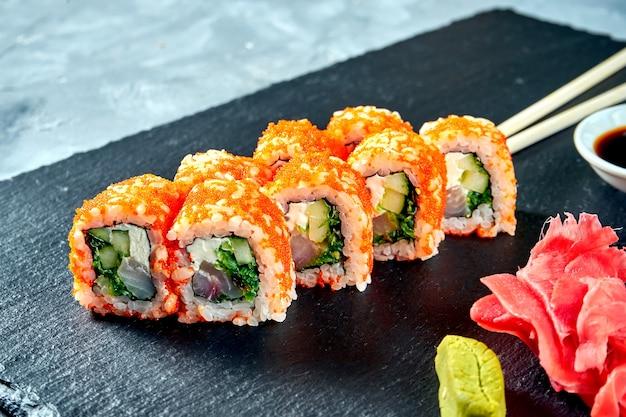 Калифорнийский суши-ролл в икре тобико с окунем, водорослями и сыром филадельфия на черной грифельной доске.