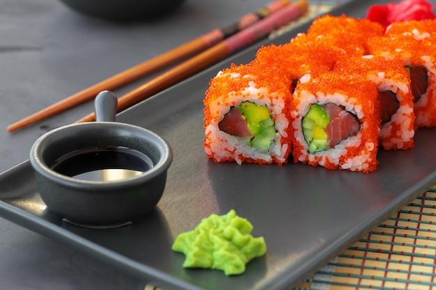 Суши-ролл калифорния на черной керамической тарелке