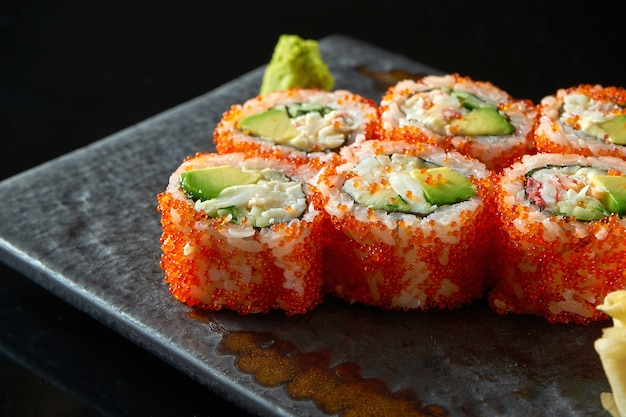 California sushi roll with crab, avocado, cucumber and tobiko caviar served on a plate with wasabi and ginger. isolation on a black table. japanese food