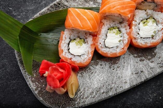 Калифорния суши-ролл с огурцом, авокадо, сливочным сыром и лососем на серой тарелке на темном столе