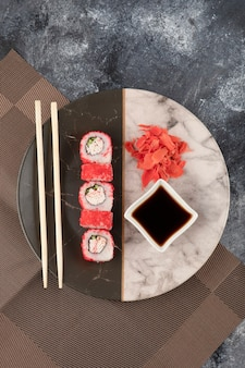 Калифорнийские суши-роллы, имбирь и соевый соус на мраморной тарелке