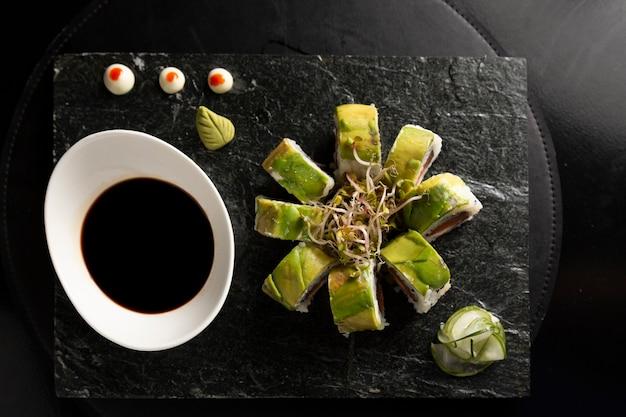 Суши-роллы калифорния в тарелке с соевым соусом