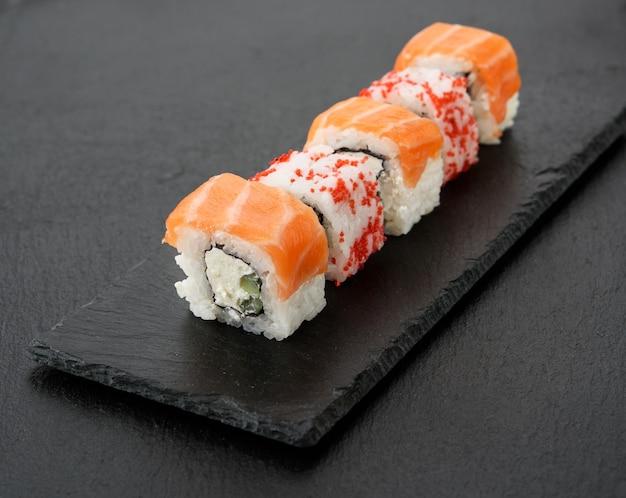 Калифорнийские суши с красной икрой тобико и кусочками суши филадельфия на черной грифельной доске, крупным планом