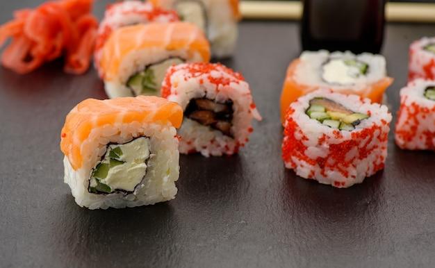 Калифорнийские суши с красной икрой тобико и кусочками суши филадельфия на черной грифельной доске, вид сверху