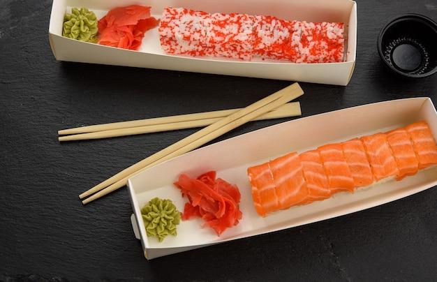 Калифорния суши с красной икрой тобико и кусочками филадельфии суши с угрем в белой коробке, доставка, вид сверху