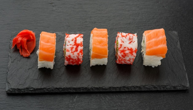 California sushi with red tobiko caviar and slices of philadelphia sushi on black slate board, top view