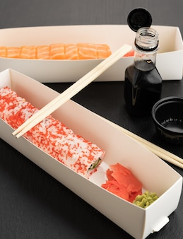 California sushi with red tobiko caviar and slices of philadelphia sushi with eel in a white box, delivery