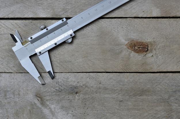 木製の背景にノギス