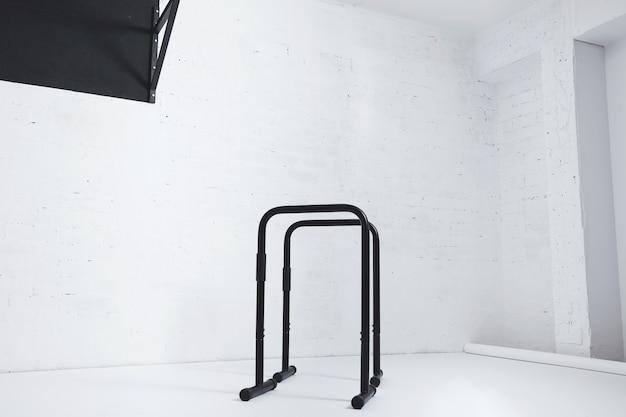 Barre parallele calisthenics isolate nella stanza bianca vuota accanto alla barra di trazione nera