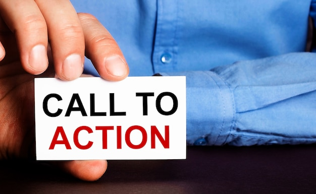 Call to action is written on a white business card in a mans hand. advertising concept.