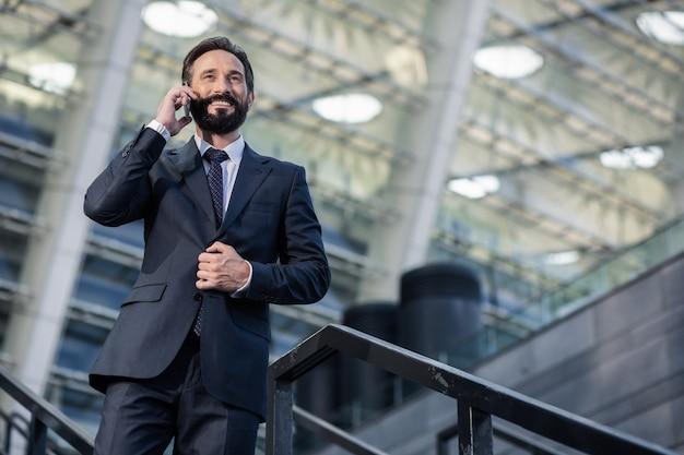 折り返し電話。電話で会話をしている楽観的なひげを生やしたビジネスマンのローアングル