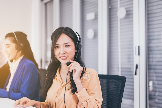 Колл-центр азиатский командный работник вместе в офисе, улыбающийся сотрудник женщина-оператор, работающий с гарнитурой