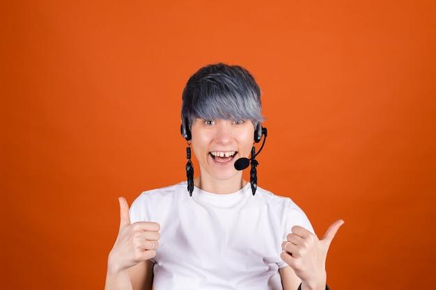 オレンジ色の壁にヘッドフォンを付けたコール センター アシスタントは、自信に満ちた笑顔で親指を立てて幸せそうに見えます