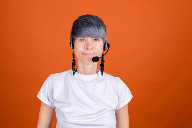 주황색 벽에 헤드폰이 달린 콜센터 도우미는 자신감 넘치는 미소로 행복하고 긍정적으로 보입니다.