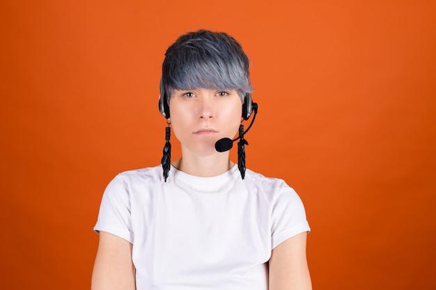 심각한 얼굴로 카메라에 얼굴을 집중시킨 주황색 벽에 헤드폰이 달린 콜센터 도우미