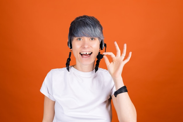 Call center assistant with headphones on orange wall look happy and positive with confident smile