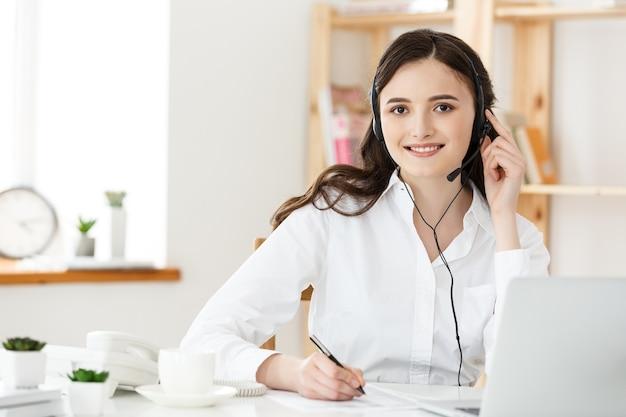 コールセンターのコンセプト:職場で幸せな笑顔の女性カスタマーサポート電話オペレーターの肖像画。