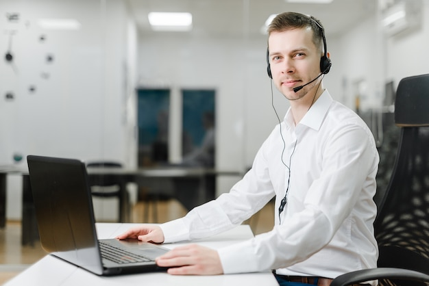 Call center operator answering business calls in the office via headset online