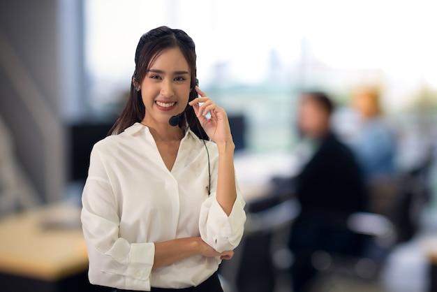 コールセンターのオペレーターは、オフィスの背景をぼかすビジネスウーマンの肖像画を技術サポートするのに役立ちます