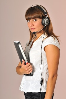 Call center woman posing with headphones and notebook on hands