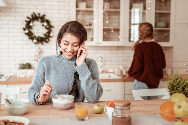 Звоните во время завтрака. улыбающаяся позитивная афроамериканская девушка разговаривает по смартфону во время еды, а ее друг остается