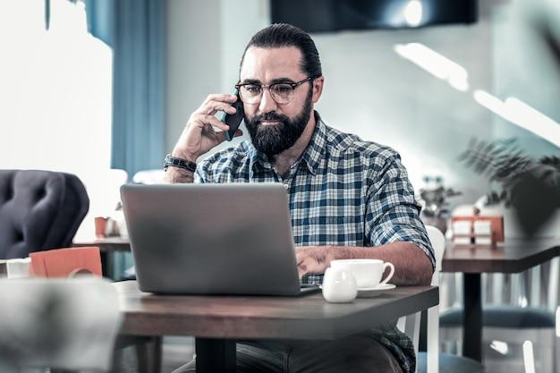 従業員に電話してください。四角いシャツを着てリモートで働いている快適な暗い目のビジネスマンが彼の従業員に電話をかけます