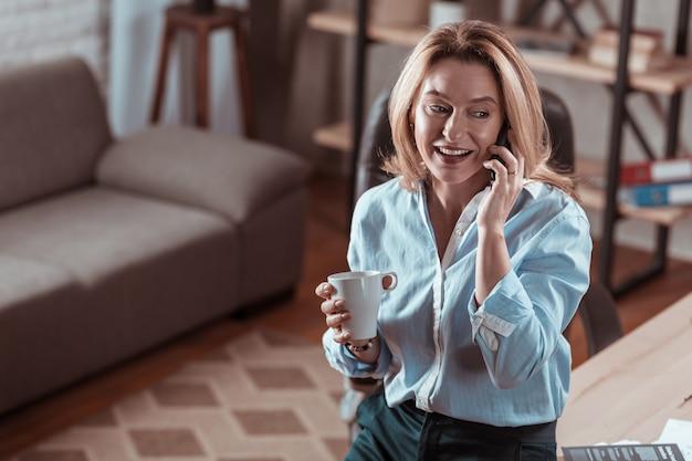 同僚から電話。青いシャツを着て同僚から電話を受け、コーヒーを飲む黒い瞳の女性