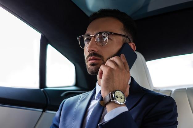 Звонок от инвестора. темноглазый бизнесмен принимает звонок от инвестора, сидя в машине