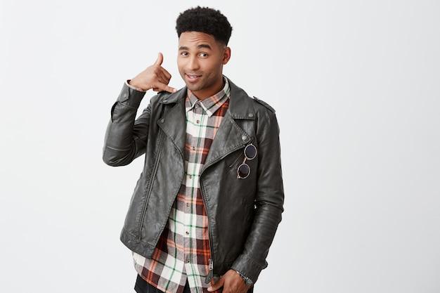 私を呼んで、ベイビー。電話番号を求めて革のジャケットに黒い巻き毛を持つ美しい陽気な若い黒肌アフリカ人の肖像画