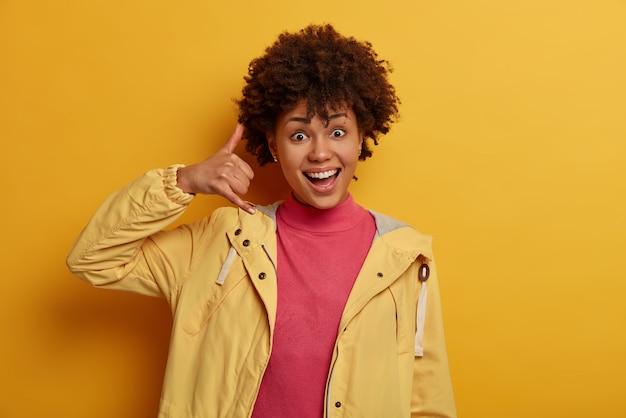 折り返し電話してください。巻き毛、耳の近くのジェスチャー、電話のジェスチャーを示し、陽気に見え、友人や親戚と接触しようとし、黄色の壁の上に屋内に立っているフレンドリーなポジティブな女性