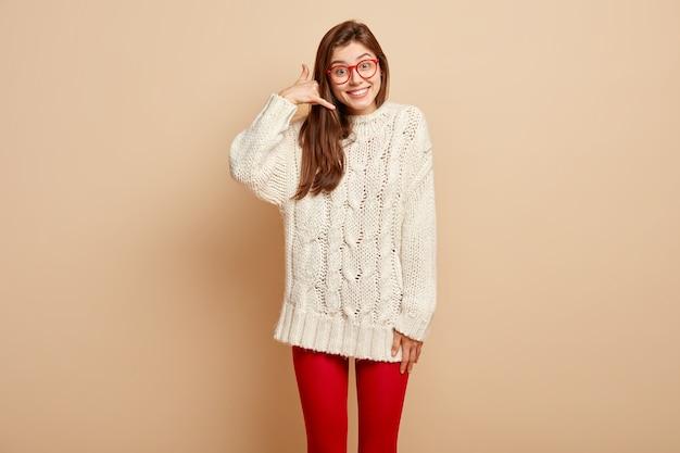 Richiamami. la bella donna positiva fa il gesto del telefono, fa il segno, chiede di essere in contatto, sorride felice, ha un aspetto amichevole, indossa un maglione invernale, isolato sul muro beige. concetto di linguaggio del corpo