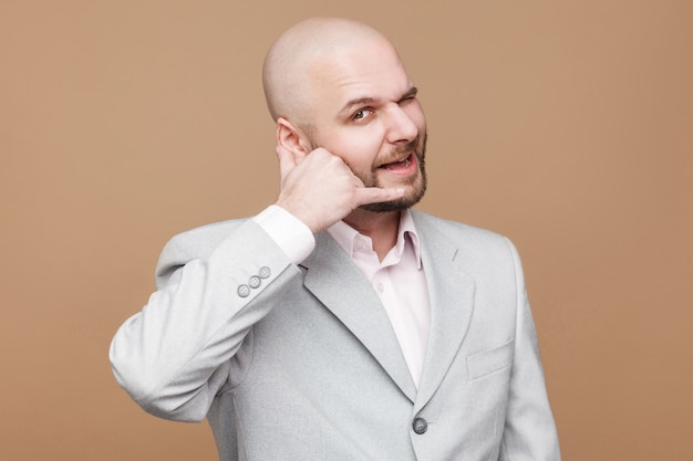 Call me please. funny handsome middle aged bald bearded businessman in classic light gray suit standing looking at camera and showing call sign. indoor studio shot, isolated on brown background.