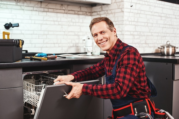 Call the professional male technician sitting near dishwasher and smiling