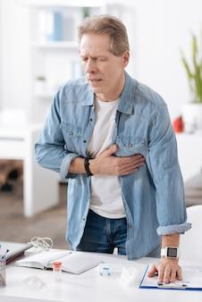 医者を呼ぶ。目を閉じたままフォルダーに左手を置いて職場の後ろに立っている心配している男性